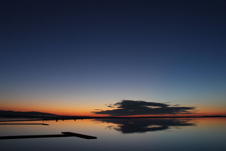 Scenic view of calm lake at dusk