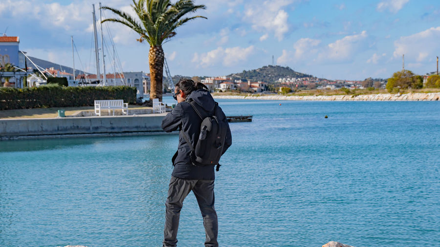 Man photographing by swimming pool against sea