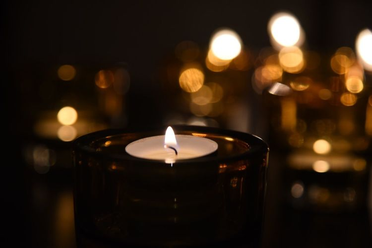 Close-up of illuminated tea light candle in darkroom
