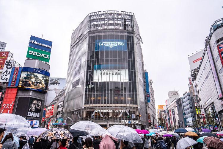 People on wet street against buildings in city