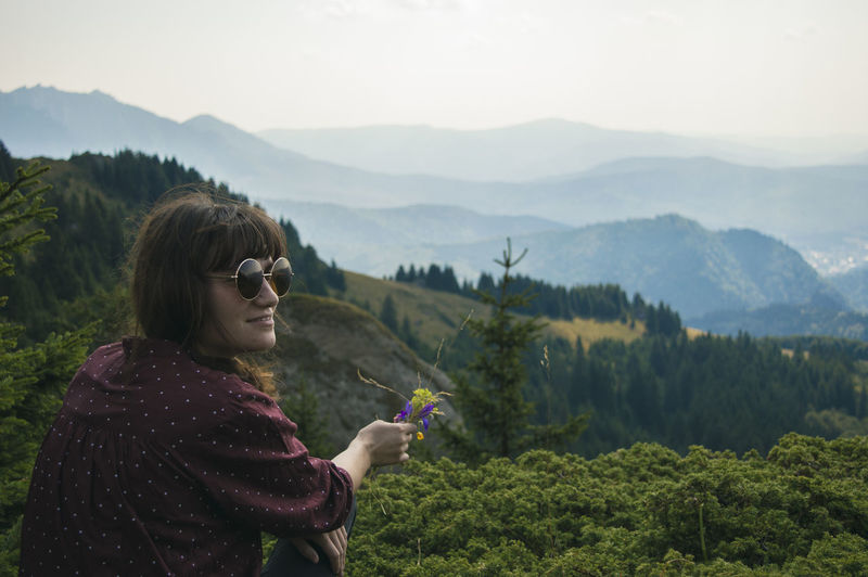 Rear view of woman looking away while sitting on mountain