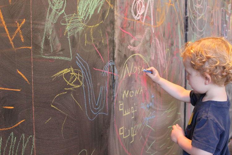 Cute boy writing on blackboard in classroom