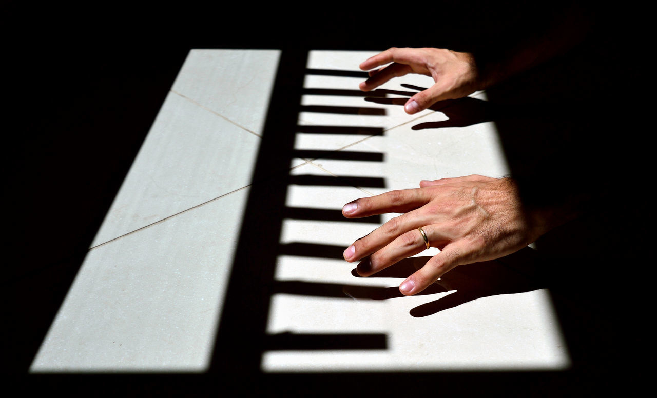Cropped hands of woman playing piano in darkroom