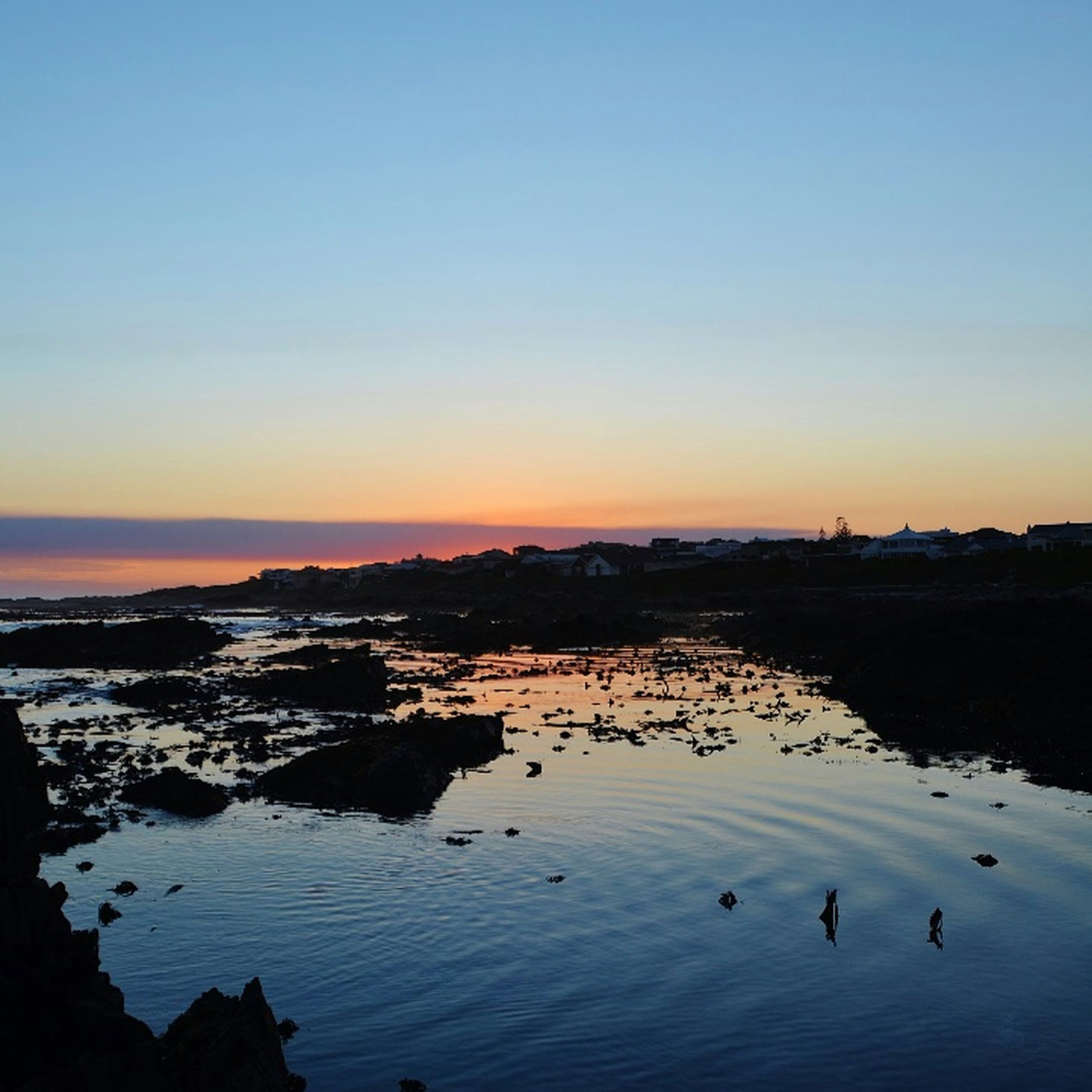water, sunset, clear sky, scenics, tranquil scene, copy space, tranquility, beauty in nature, sea, silhouette, nature, idyllic, reflection, beach, shore, sky, horizon over water, dusk, outdoors, calm
