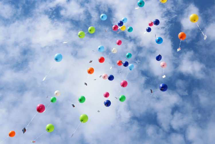 Low angle view of helium balloons against cloudy sky