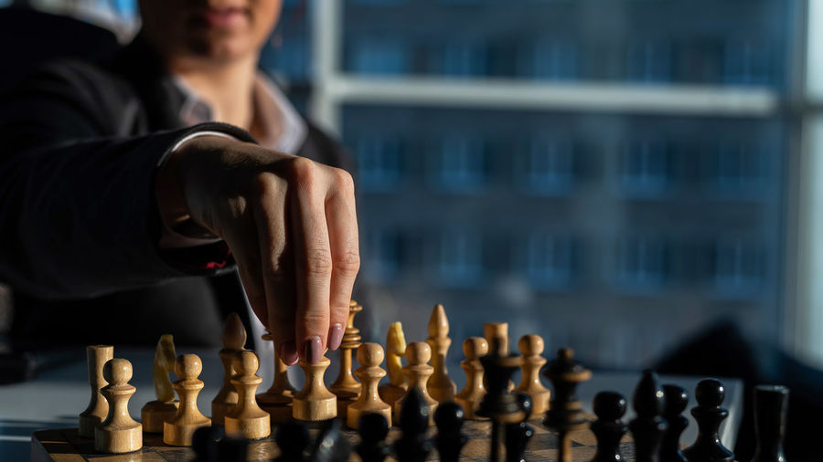 Midsection of man playing on chess board