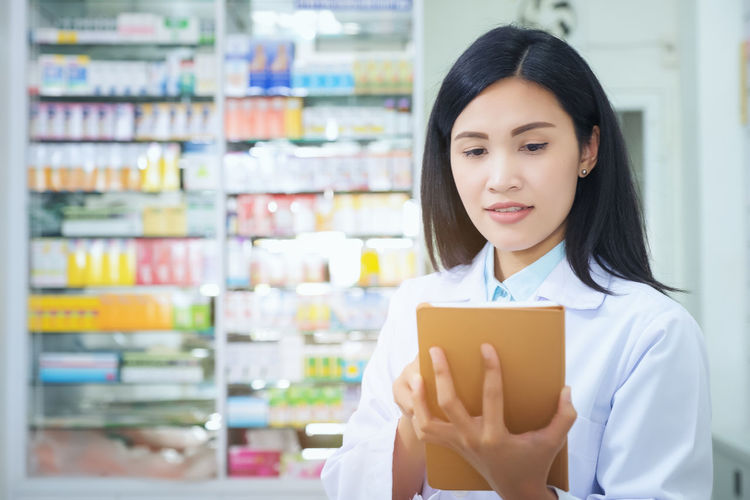 Pharmacist working with a tablet computer in the pharmacy holding it in her hand while reading information One Person Adult Indoors  Front View Women Holding Choice Retail  Young Adult Store Shelf Young Women Portrait Looking Focus On Foreground Business Hair Real People Beautiful Woman Hairstyle