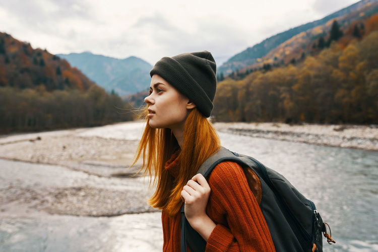 Beautiful young woman looking away while standing on mountain