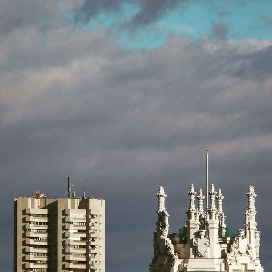 High section of buildings against cloudy sky