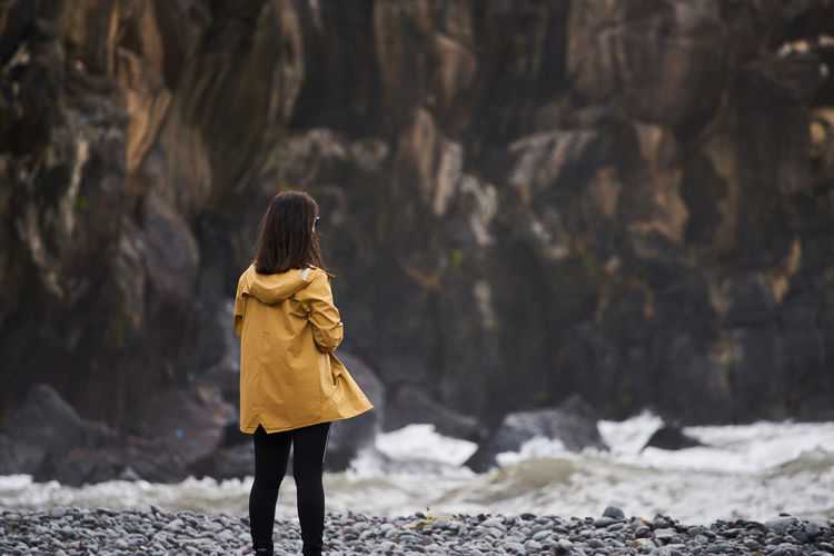 Woman on a yellow rain jacket looking to the sea with rocks on the background, in Madeira Alone Lonely Madeira Nature Portugal Portuguese Travel Woman Yellow Jacket Beach Camara De Lobos Cliff Girl Island Jacket Landscape Nature Outdoors Rock Sea Seascape Traveler Waves Women Yellow
