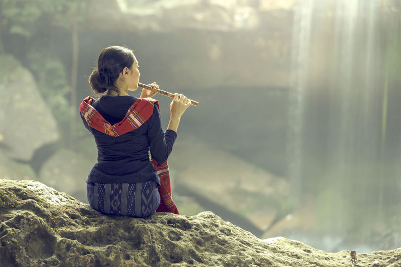 Rear view of woman playing flute while sitting on rock against waterfall