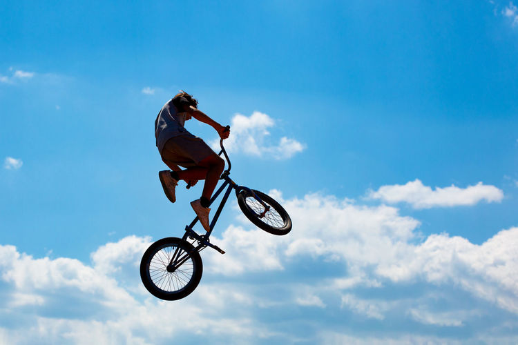 Silhouette of man jumping on bicycle against blue sky with white clouds. guy performs tricks on bike