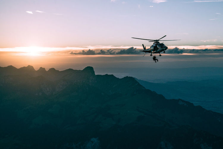 Helicopter flying over mountains against sky at sunset