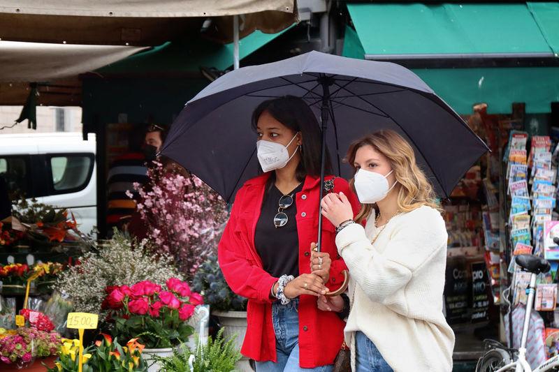 Woman holding umbrella at market stall