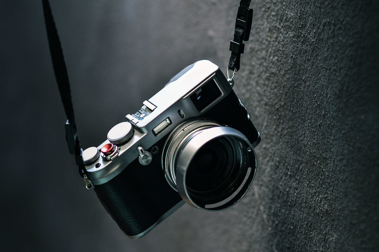 Close-up of camera hanging by wall