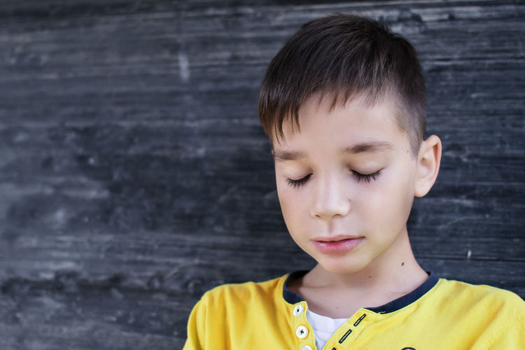 Close-Up Of Boy With Eyes Closed By Black Wooden Wall