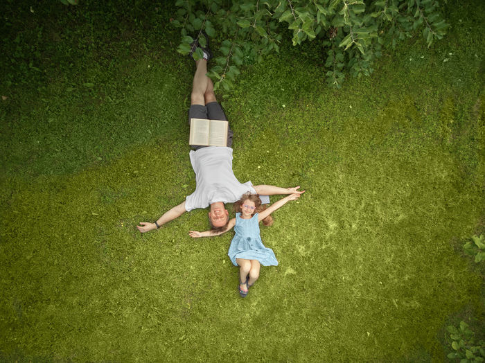 Full length of happy young woman lying on grass