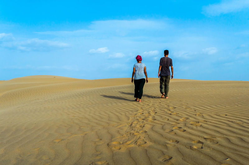 We capture this moment while exploring the Thar Desert in Northem India, just outside of the ancient city of Jaisalmer. Travel Couple Traveling Travel Photography Travel Outdoors Couple - Relationship Beauty In Nature Real People Lifestyles Cloud - Sky Arid Climate Sand Dune Climate Men Rear View Scenics - Nature Togetherness Adult Women Nature Landscape Two People Desert Sky Sand Land