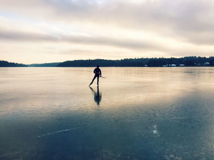 Rear View Of Person Skating On Frozen Lake Against Sky
