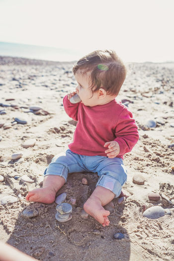Boy sitting on pebbles at beach
