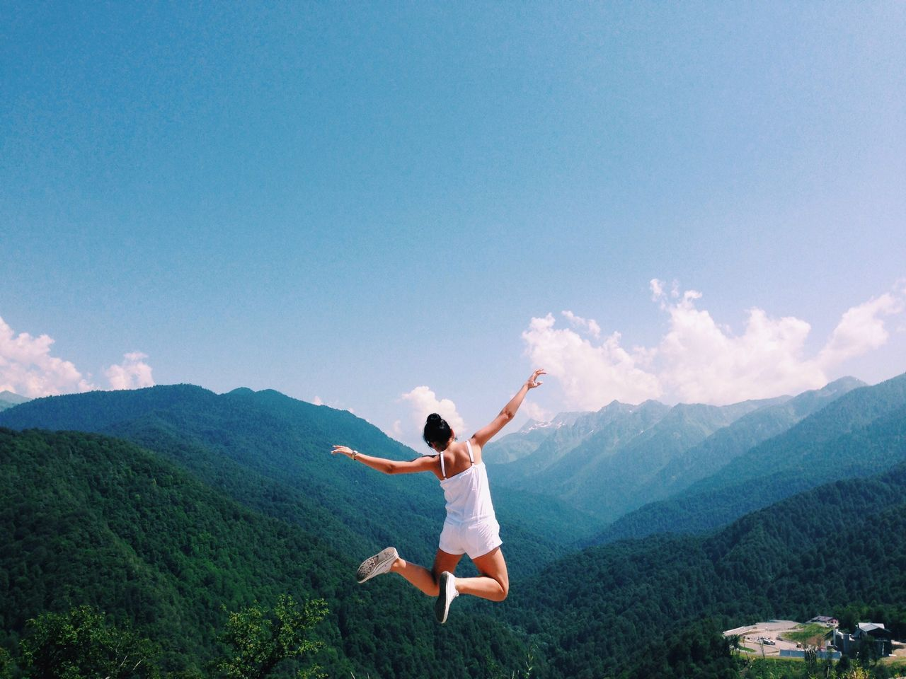 Woman jumping against mountains