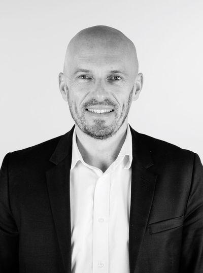 Portrait Of Smiling Bald Businessman Against White Background