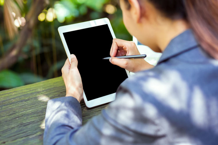Midsection of woman using digital tablet on table while sitting outdoors