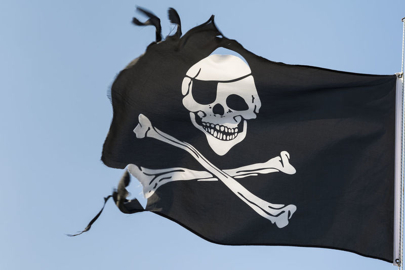 Torn pirate flag against the blue sky Anarchy Crime Evil Fear Pirate Retro Waving Adventure Bad Concept Damaged Danger Dangerous Emblem  Flag Grunge Jolly Old Piracy Ripped Robber Skulls And Bones Torn Warning Wind