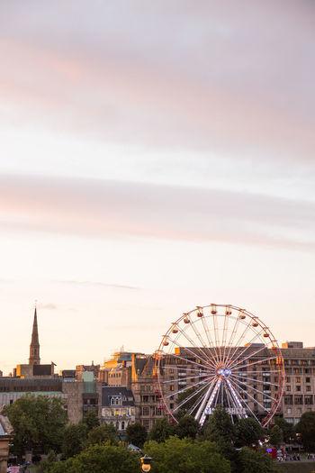 Ferris wheel in city against sky during sunset