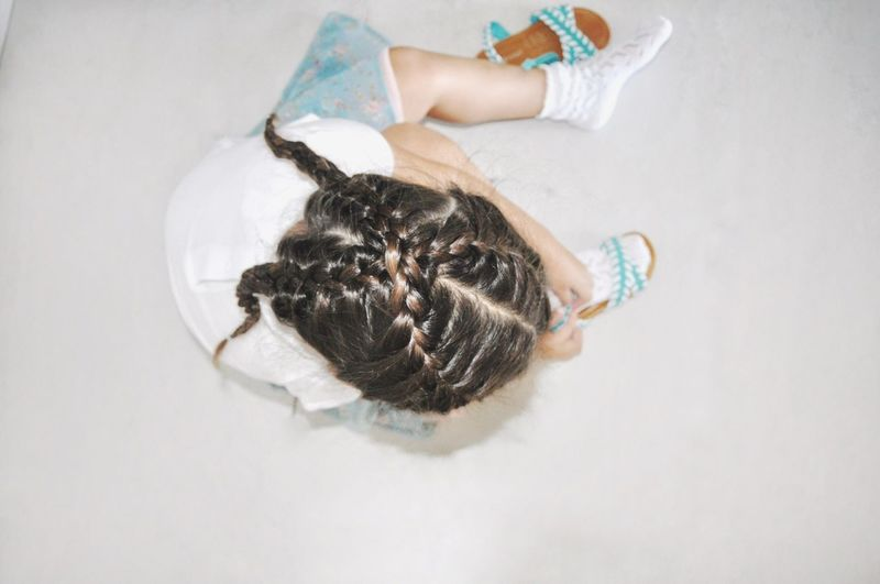 Directly Above Shot Of Girl Wearing Shoe While Sitting At Home