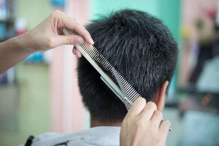 Rear view of man getting haircut