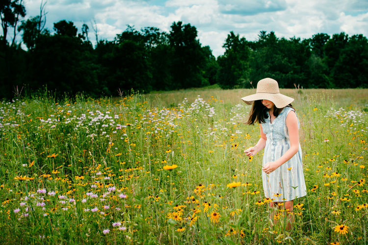 Side view of girl standing in field by flowering plants