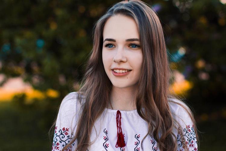Smiling beautiful young woman looking away outdoors
