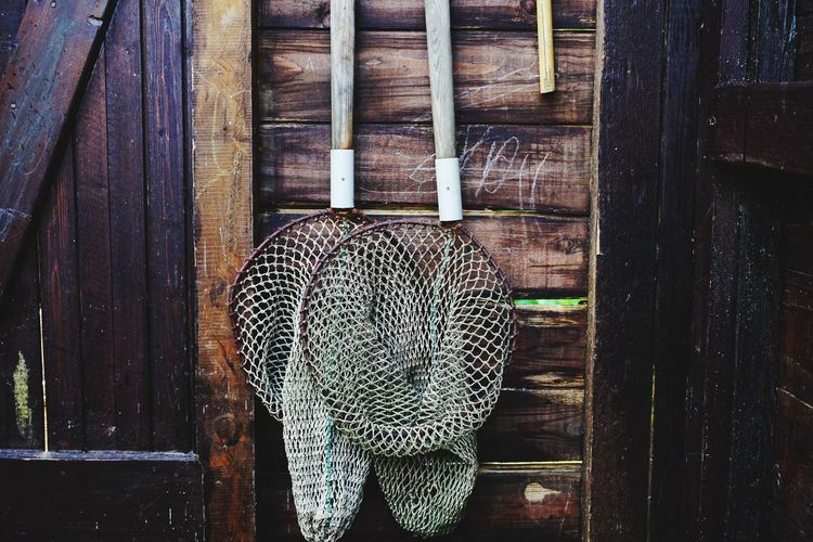 Close-up of wicker basket hanging on wooden wall