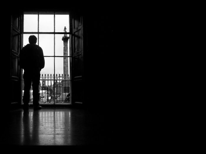 A man in  silhouette standing in front of a window