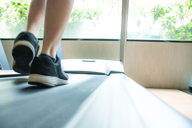 Low section of woman exercising on treadmill in gym by window
