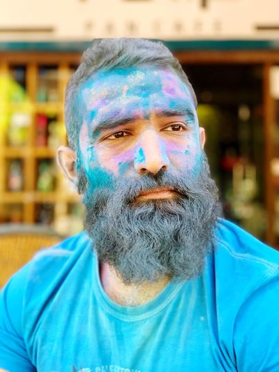 Close-up portrait of bearded man covered in powder paint