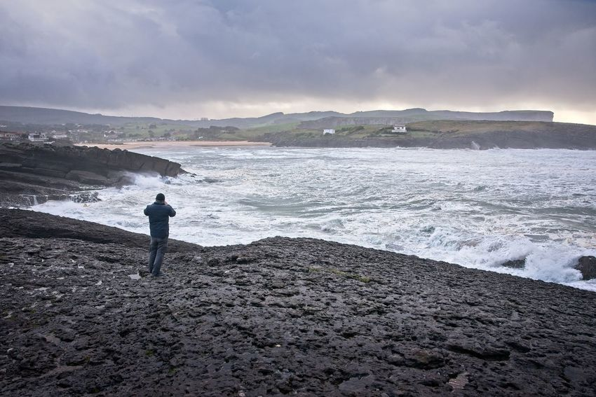 A man takes pictures of the sea during the storm Alone Cantabria Man Seashore Storm Surf Taking Photo Travel Ajo Bareyo Beach Clouds Cuberris Landscape Ocean One Person person Photo Photographing Rocks Sea Seascape Smartphone Storm Cloud Tourism
