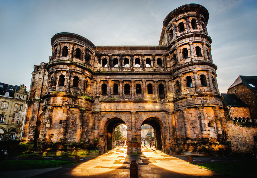 The Porta Nigra (Black Gate) in Trier city, Germany. It is a famous large Roman city gate. Front view. UNESCO World Heritage Site Ancient Arch Architecture Building City Evening Exterior Famous Place Germany Historical Building Impressive Landmark Monument Old Town Outdoors Porta Nigra Sunlight Sunset Towers Travel Destinations Trier City UNESCO World Heritage Site Unrecognizable People Western Europe