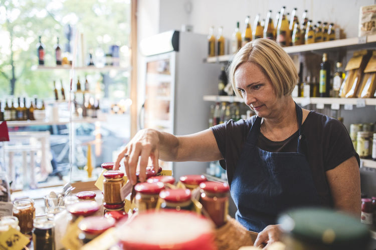 Mature female employee arranging jars in deli