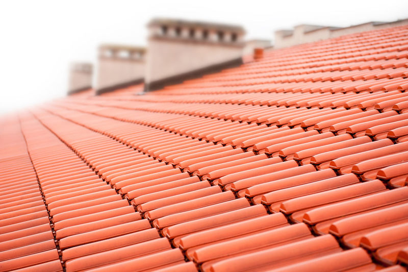 Overlapping rows of red tiles roof with chimneys in Poland, ridge tiling material regular pattern background in horizontal orientation, nobody. Backgrounds Chimney Chimneys Close-up Day In A Row No People Overlapping Red Ridge Roof Roof Tile Rooftop Rows Tile Tiles