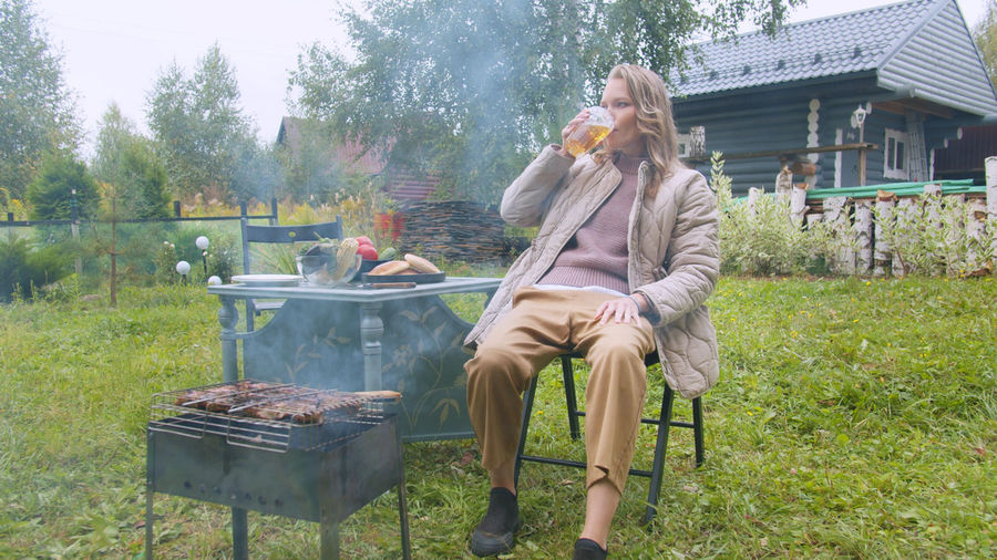 Man sitting on barbecue grill