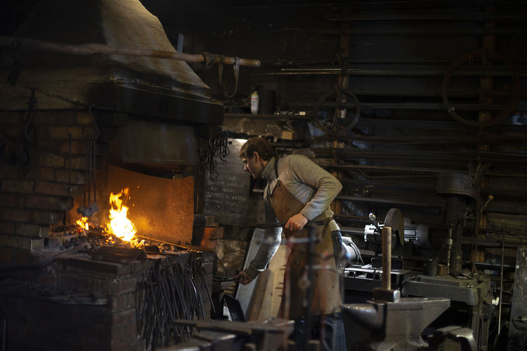 Latvian blacksmith working with open fire in furnace. the blacksmith forging hot iron in workshop