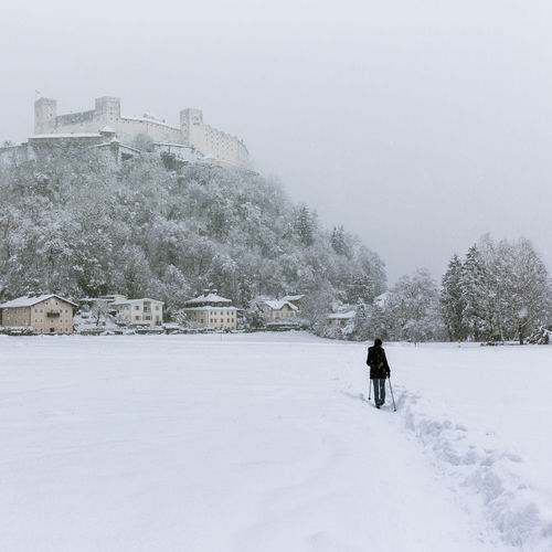 Person standing on snow covered landscape