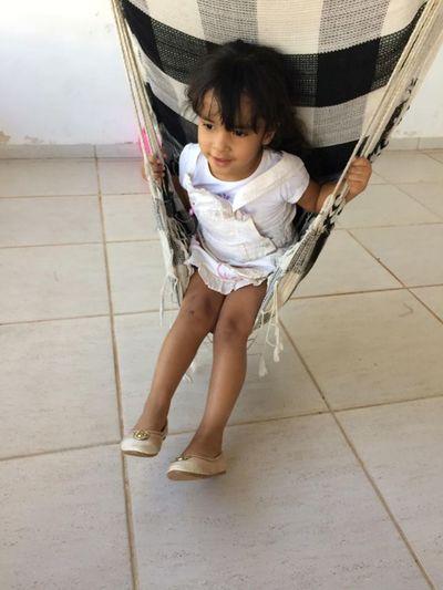 Girl sitting on hammock at home