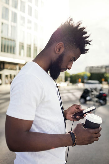 Side view of young man using mobile phone while standing on street