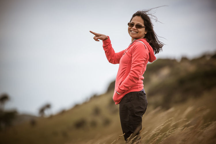 Young smiling woman pointing while standing on grassy hill