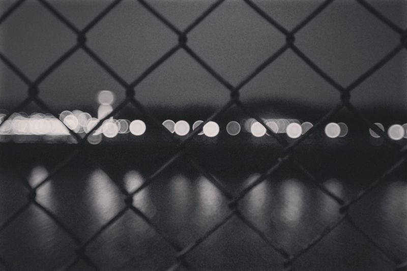 Defocused image of chainlink fence against sky at night