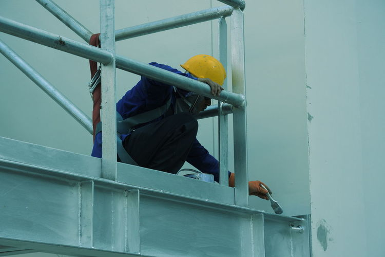 Construction worker painting railing