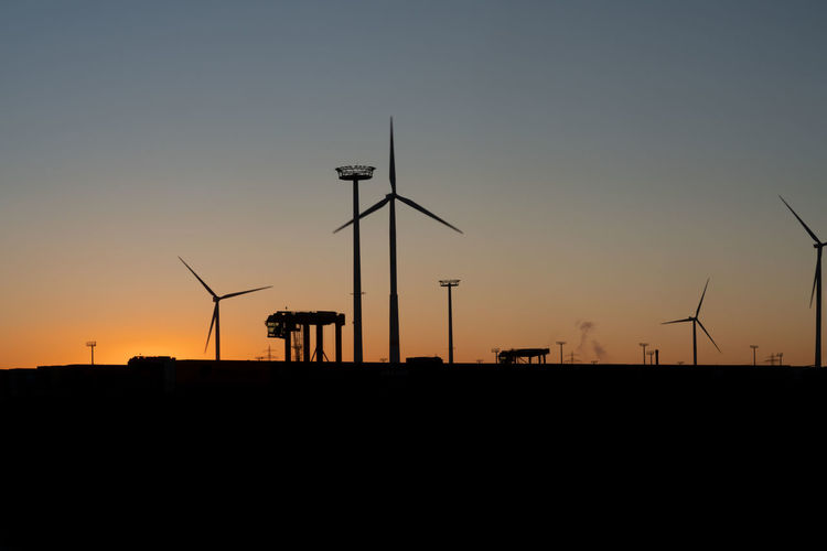 Silhouette of wind turbine against sky during sunset